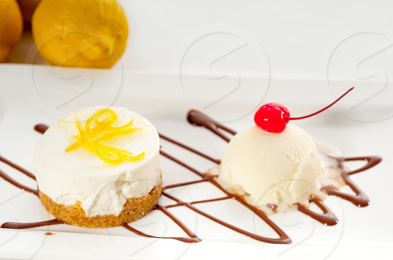 very elegant lemon mousse dessert served whith lemon peel on top and vanilla ice cream on side MORE DELICIOUS FOOD ON PORTFOLIO photo