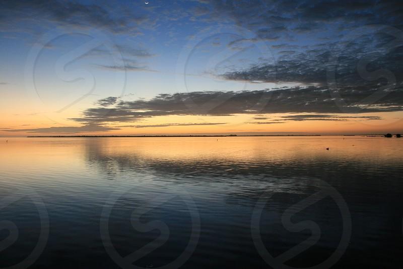Sunset island clouds sky water reflection moon orange blue dusk horizon photo