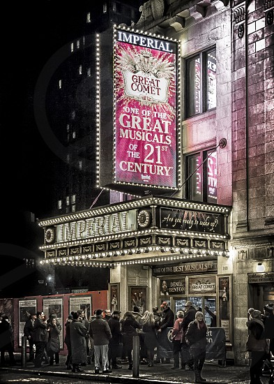 Broadway theater marquee brightly lit at night.  Crowd mingling below marquee. photo