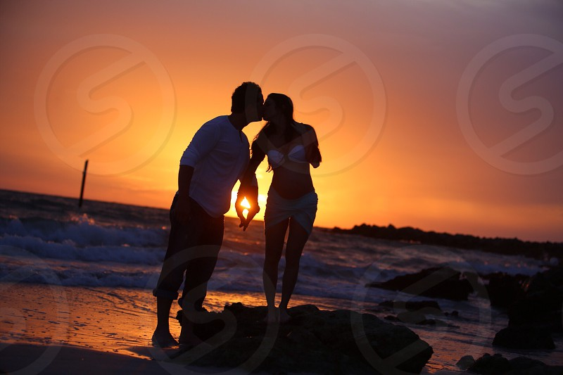 man and woman kissing on beach in sunset view photo