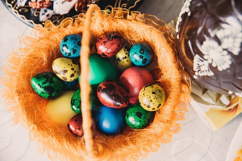 Colourful quail eggs in Easter basket photo