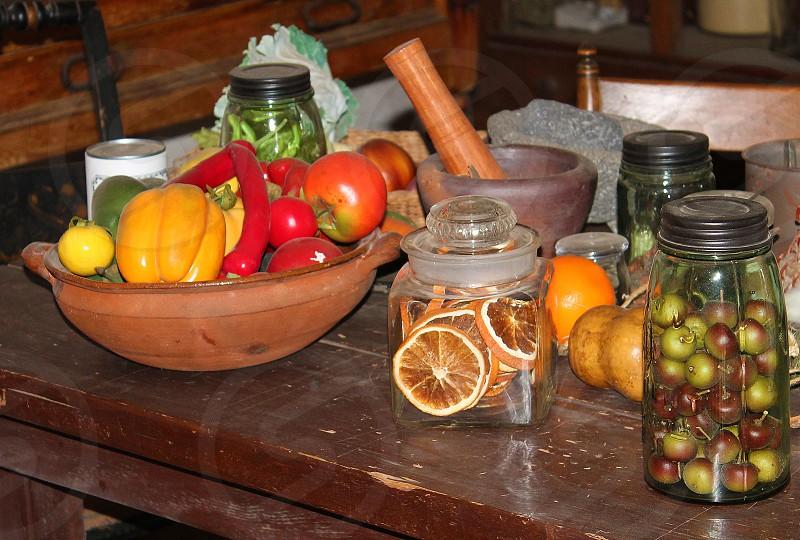 Fresh vegetables are in a wooden bowl and fruits are in canning jars; all are on a wooden farm table. photo