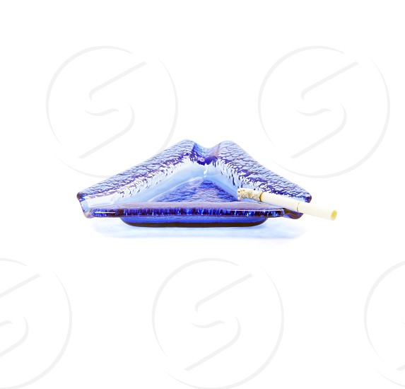 blue murano glass ashtray with lighted cigarette isolated on white background photo