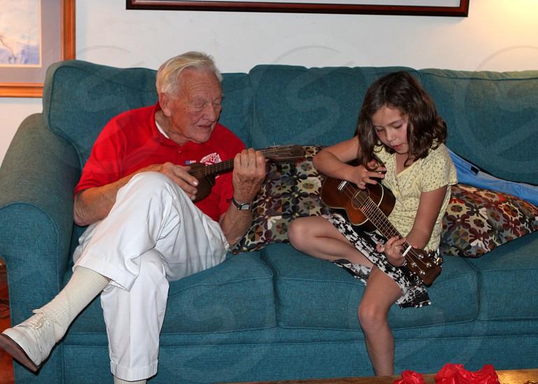 man and girl playing ukulele on couch photo
