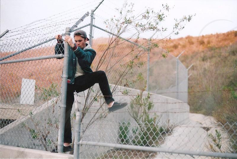 man in black pants climbing on gray metal fence photo