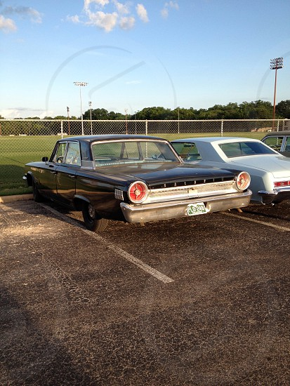 Vintage cars in a football parking lot.  photo