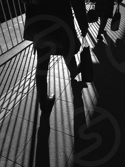 person walking on brown floor tiles photo