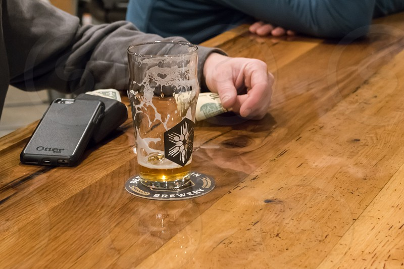 A patron enjoying a glass of beer at the Beehive Brewery in Montana photo
