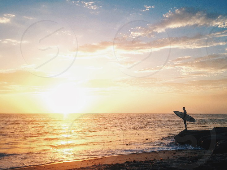 man carrying surfboard looking over at sunset photo