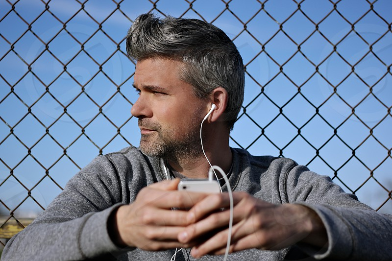 man in grey sweater listening to ipod photo