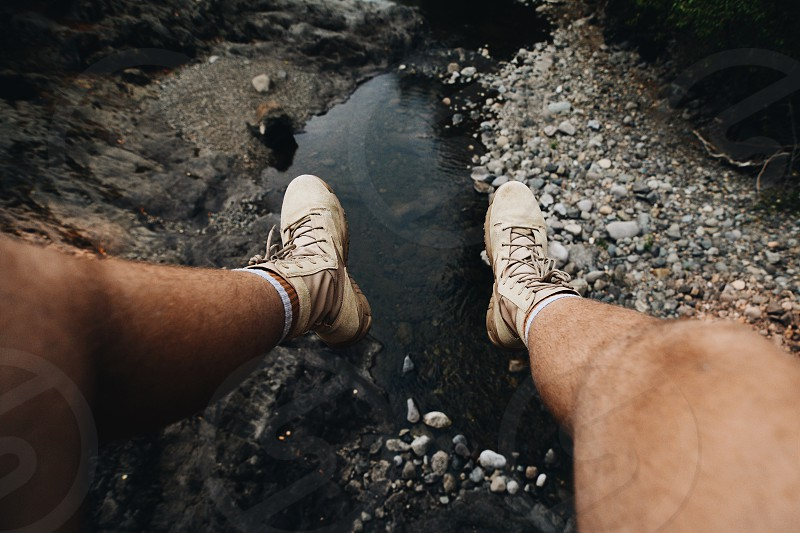 person wearing brown lace up work boots seating in front of running water photo