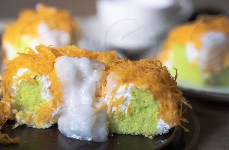 "close up selective focus piece of  Gold Egg Yolk Thread Cake  or  'Cake Foi Tong"" Thai pandan cake  with delicious young coconut cream on white plate with blurred white coffee cup in background copy space photo"