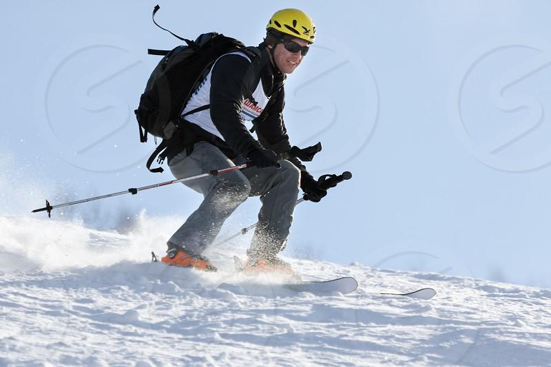 KRASNAYA SOPKA PETROPAVLOVSK CITY KAMCHATKA RUSSIA - FEB 4 2012: Ski mountaineer rides skiing on mountain on background of blue sky. Ski-mountaineering competitions - Cup Petropavlovsk-Kamchatsky. photo
