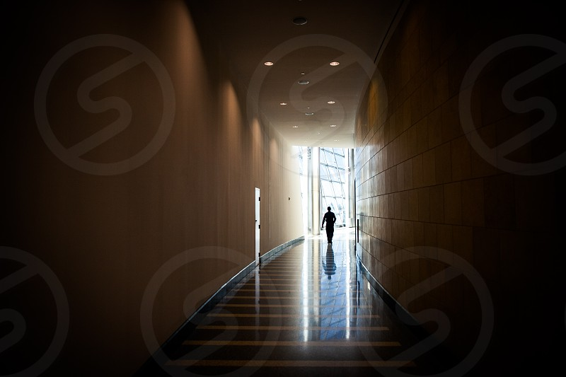 A silhouetted figure walks through a dimly lit hallway toward a bright window. Contrast intense stark geometry architecture lights reflection tile person human negative space. photo