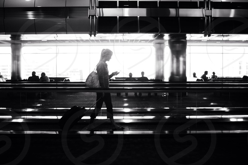 woman in white hand bag walking with black luggage bag photo