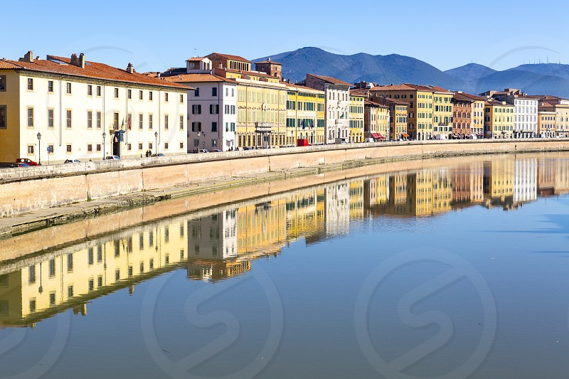 Pisa city centre in Italy with buildings reflected in the Arno River photo
