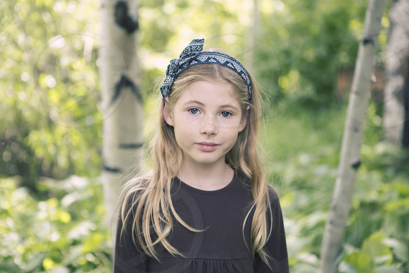 childkid girl 9 years old blonde long hair head band bow nature green aspens colorado mountains sweet innocent portrait natural lighting pretty little girl smile blue eyes brown shirt landscape trees wild hiking exploring playing outside  photo