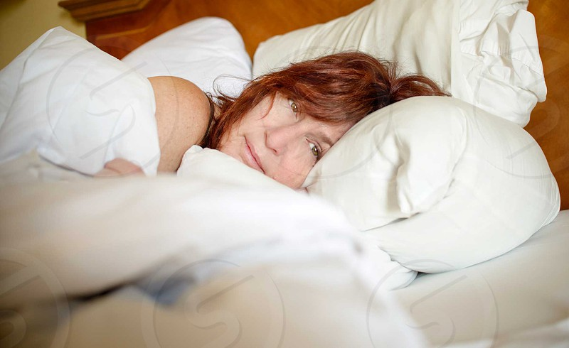 smiling brown haired woman lying on bed under white blanket photo