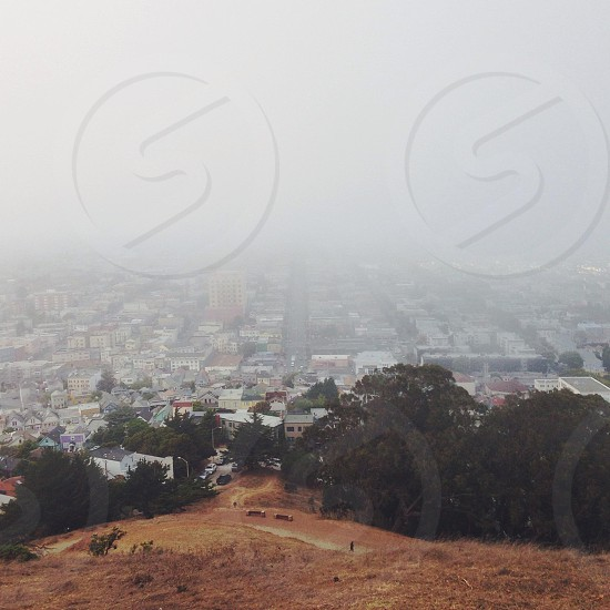 large city down below brown rolling hills and tree photo