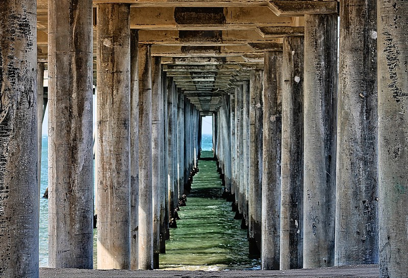 Looking through the wooden pylons and poles of a pier on a beach photo