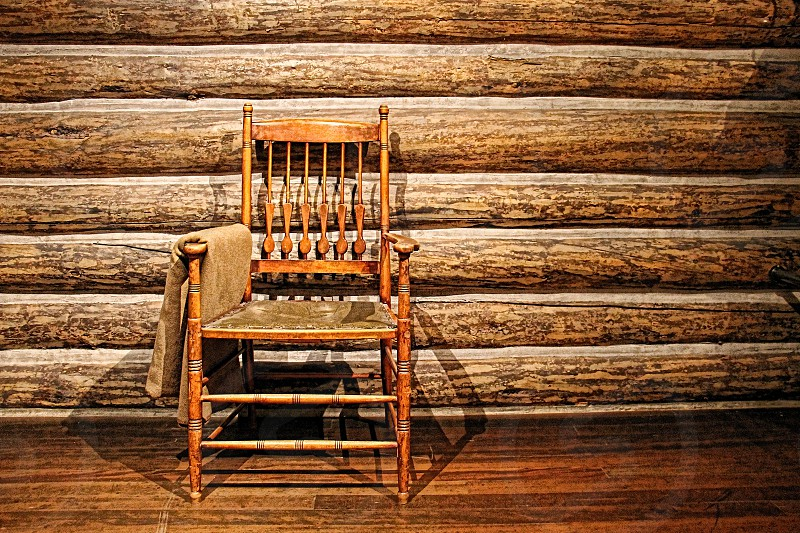 A wooden chair in the interior of a log cabin photo