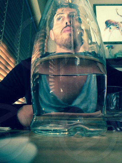 Man looking through a vase pitcher of water reflection  photo