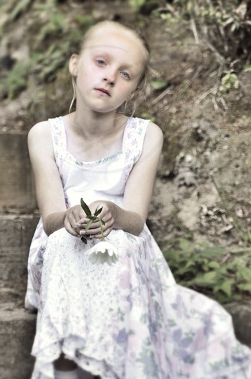 Drooping child with drooping daisy  photo
