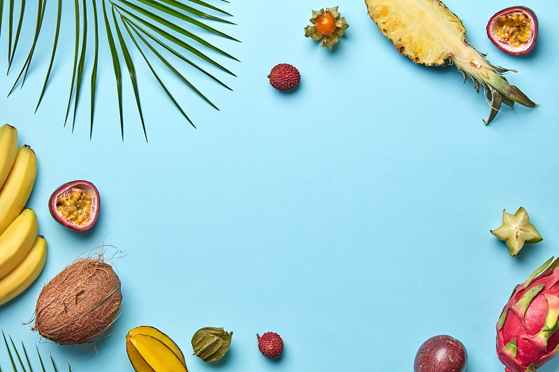 Coconut banana carambola physalis and green palm leaf on a blue background with copy space. Creative Food frame. Flat lay photo