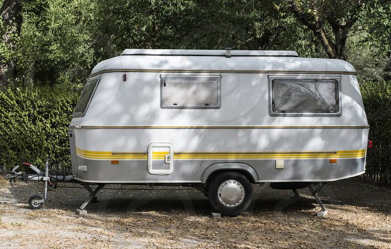 Small caravan on campsite. Green bushes photo
