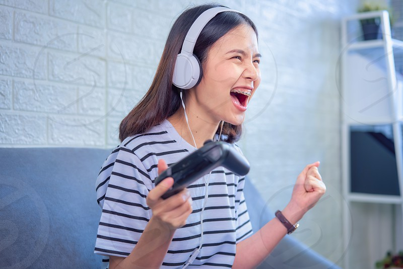 Excited young Asian woman sitting on sofa wear white headphone on the head and playing games in the living room at home. photo