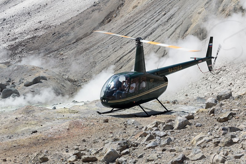 MUTNOVSKY VOLCANO KAMCHATKA RUSSIA - JULY 4 2014: Touristic Helicopter Robinson R44 Raven with travelers and tourists on board standing by in crater of active Mutnovsky Volcano on background of smoking (steaming) fumaroles. Eurasia Russian Far East Kamchatka Peninsula. photo