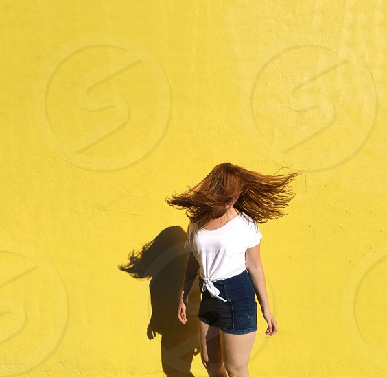 woman in white t shirt in front of yellow wall photo