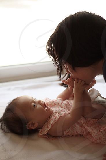 woman kissing baby's feet photo