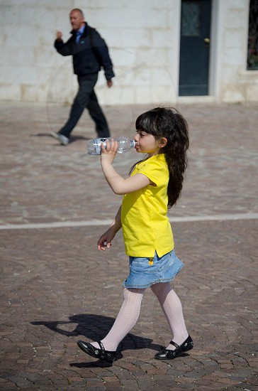 girl with black long hair in yellow polo shirt and gray denim skirt drinking water from bottle photo