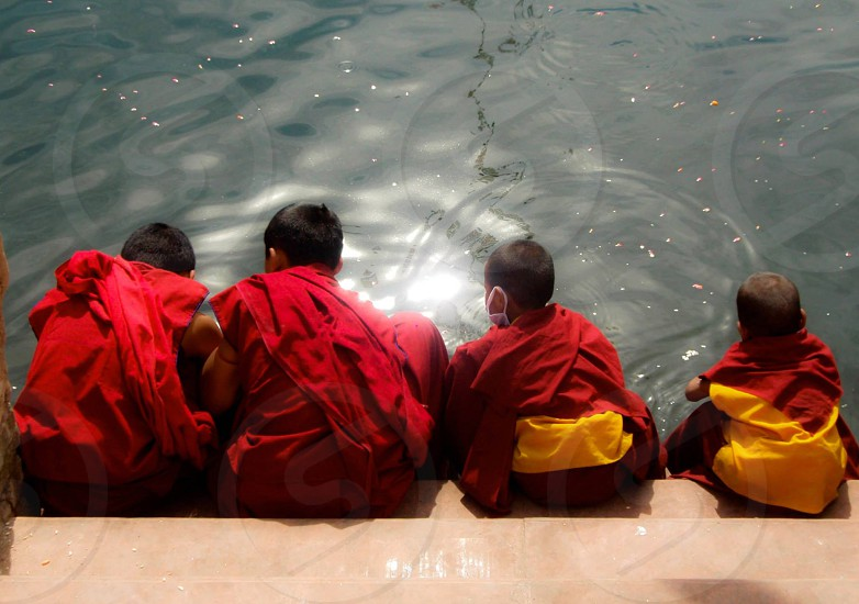 four children in red top sitting on front of body of water during daytime photo