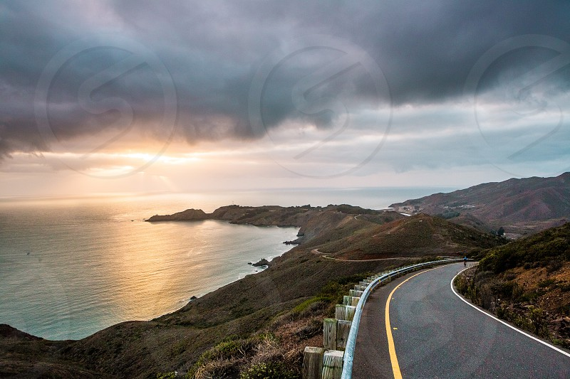 grey and pink cloudy sky at sunset over ocean and black paved road curving down hill photo