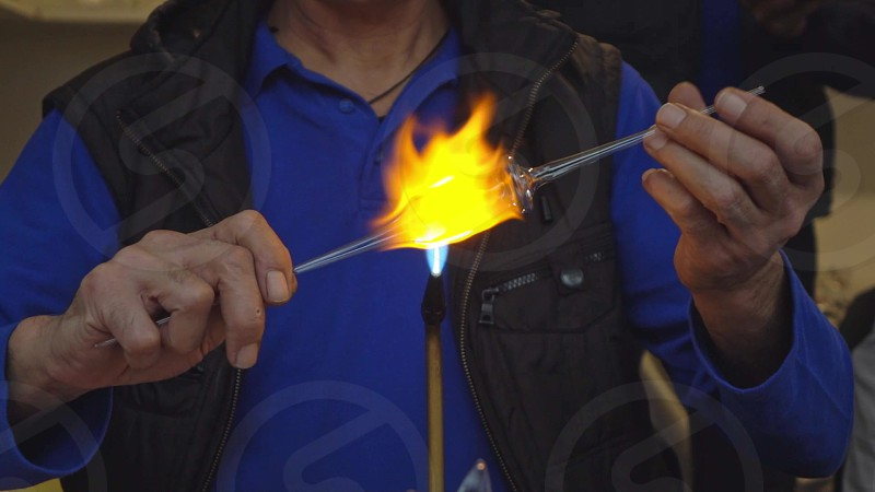 Professional glassblower in a handmade process of creating craft glass products on a manufacturing factory step by step. Molten glass with open fire. Slow motion Full HD video 240 fps 1080p. photo