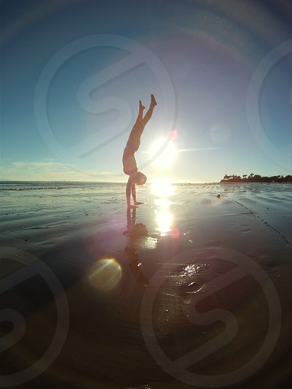 Sandy hand stands on the beach photo