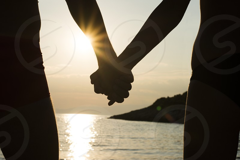 Man and woman holding hands at sunset on a beach photo