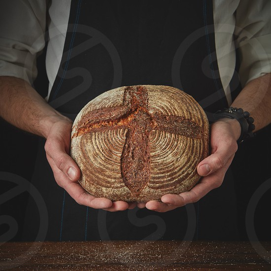 Close-up of a man's hand holding a round dark bread photo