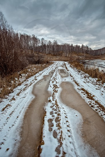 Road on the first autumn snow on the forest lake with grey clouds photo