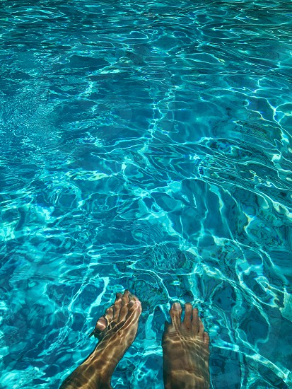 person's feet under the water photo