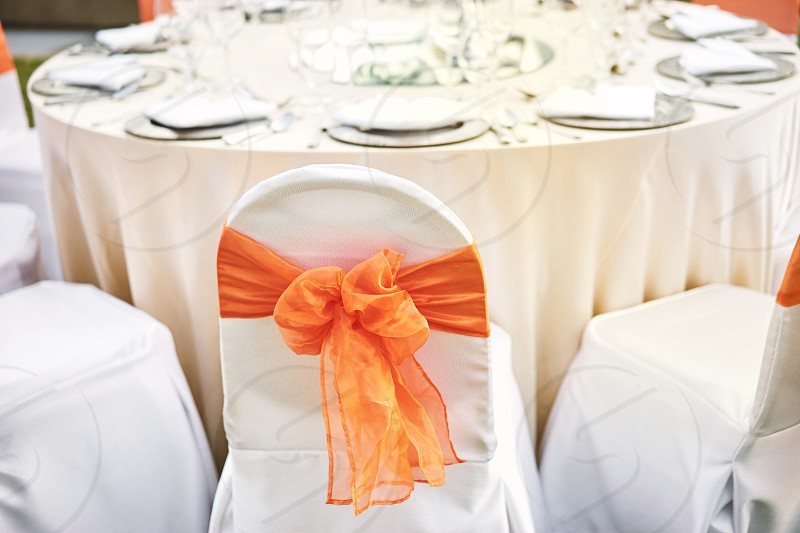 Luxury wedding reception dinner table setting with spandex white cover chairs with orange organza sash photo