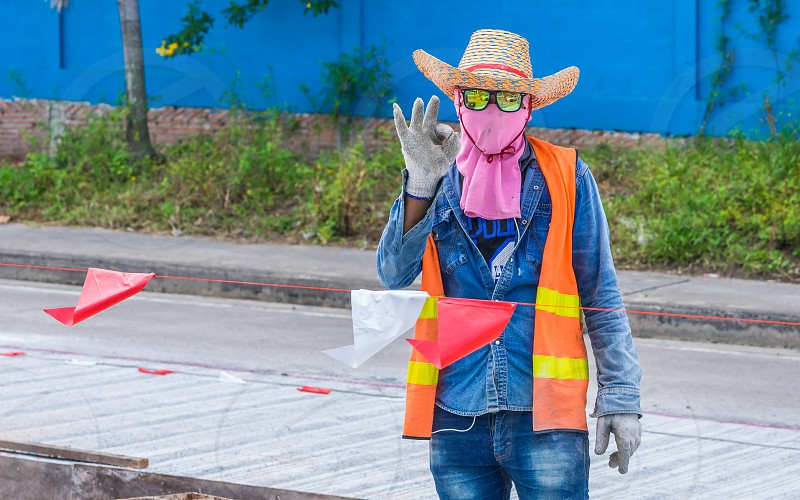 A road construction worker in colourful clothes in Thailand. photo