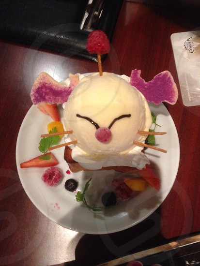 A desert from a Japanese cafe in Tokyo. Uses crackers ice cream and berries to look like a character from Final Fantasy (moogle). Ice cream on honey toast photo