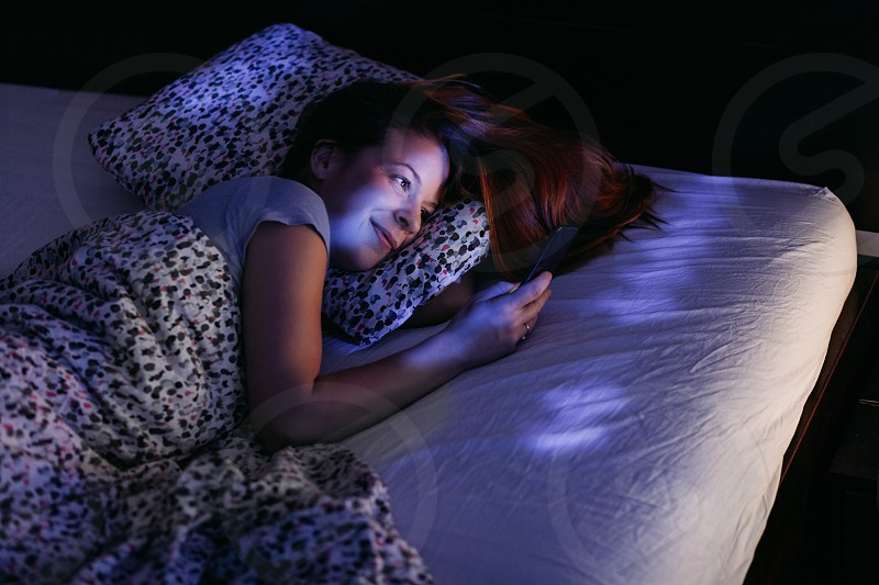 Young woman using smartphone in bed at night photo