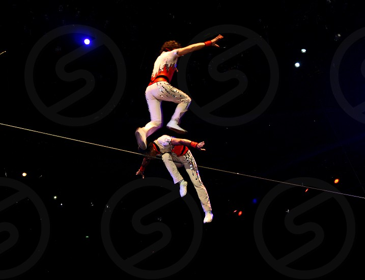 A tightrope walker is leaps in midair over his high wire partner. photo