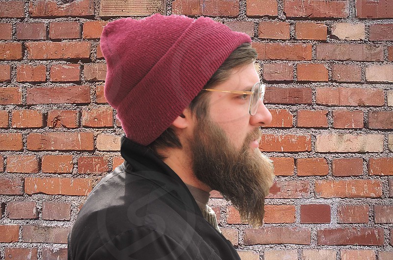 man wearing burgundy beanie and glasses in front of brick wall photo