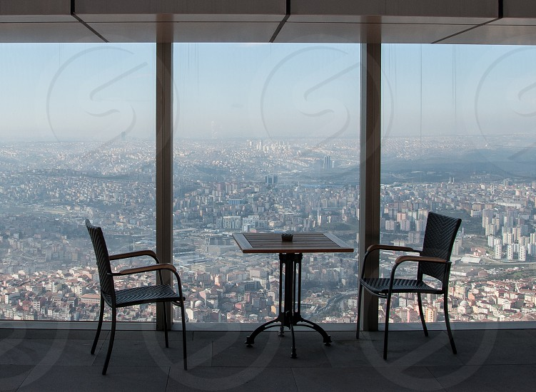 2 metal chairs and a table with the city view photo