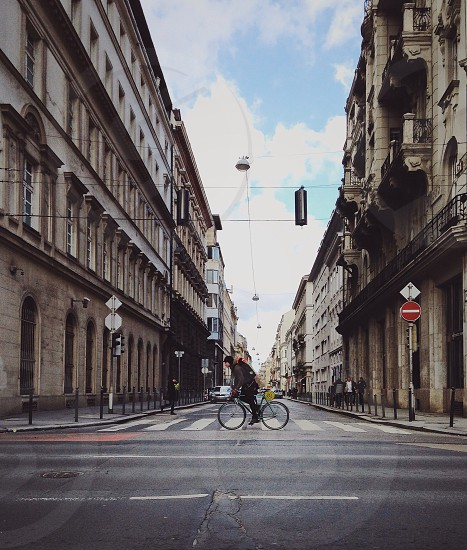 person in black jacket riding bicycle crossing pedestrian lane under blue and cloudy sky during daytime photo